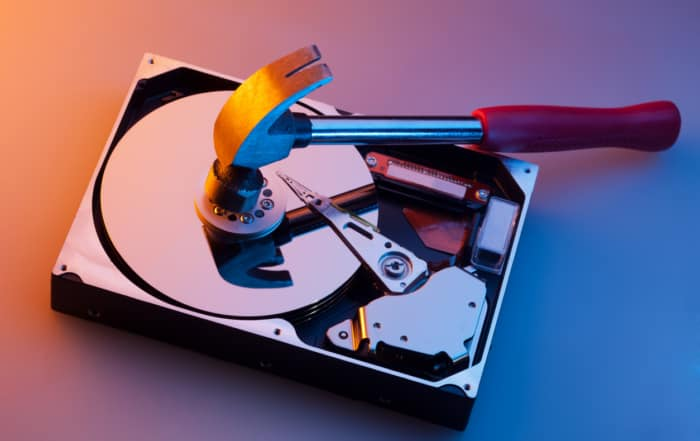 Image of hammer crushing disk drive to illustrate data destruction